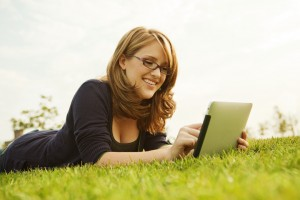 Girl lying in grass using computer tablet